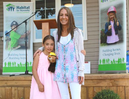 Megan Johnson and her eight-year old daughter Tori stand in front of their new Habitat for Humanity Home in Sarnia on July 31. Johnsons' 1,080-sqaure foot Habitat home was built in partnership with Lambton College students and faculty, who, along with volunteers, completed the construction that began last September. (CARL HNATYSHYN, QMI Agency)