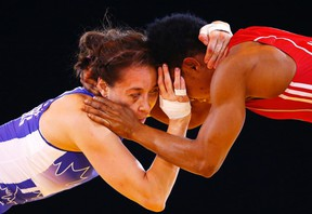 Brittanee Laverdure of Canada (left) and Ifeoma Nwoye of Nigeria grapple during their women's freestyle 55kg wrestling semifinal at the Commonwealth Games in Glasgow, Scotland, on Thursday, July 31, 2014. (Andrew Winning/Reuters)