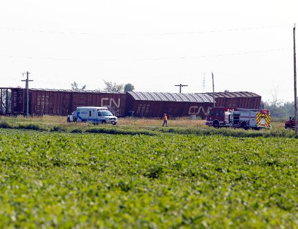 An ambulance and fire truck sit at the scene of a Via Rail CN freight train collision east of Gananoque on Friday afternoon. There were reports of one minor injury in the collision, which forced six freight cars of the track (NICK GARDINER/The Recorder and Times).
