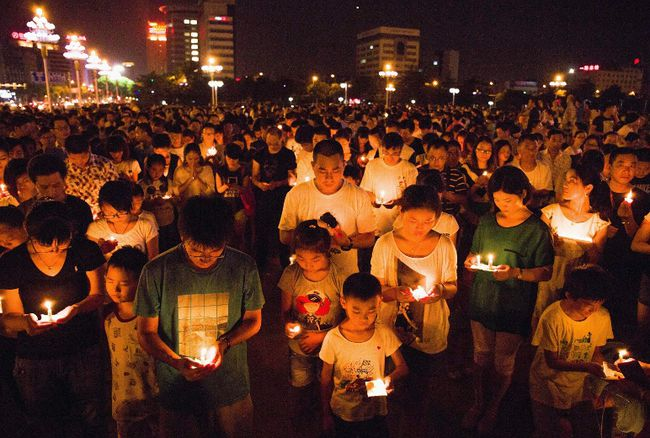 Residents gather as they attend a candlelight vigil for victims of a factory explosion, in Kunshan, Jiangsu province Aug. 2, 2014.  REUTERS/Stringer