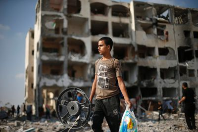 A Palestinian carries his belonging as he walks past a badly damaged residential building after returning to Beit Lahiya town, which witnesses said was heavily hit by Israeli shelling and air strikes during the Israeli offensive, in the northern Gaza Strip August 5, 2014.  REUTERS/Suhaib Salem