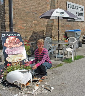 Michelle Beuerman displays the damage caused on her business property, the Fullarton Corner Store, at Line 20 and Perth Road 163 in Fullarton last Wednesday, July 30. Traffic and in particular, large trucks using the intersection for right-hand turns has been an issue for several years and has caused safety concerns for children and adults, as well as property damage on more than one occasion. KRISTINE JEAN/MITCHELL ADVOCATE