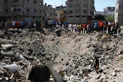 People look at a crater on the ground and damaged buildings, that witnesses said was caused by an Israeli air strike, in the Zeitoun neighbourhood in Gaza City August 8, 2014. Israel launched air strikes across the Gaza Strip on Friday in response to Palestinian rockets fired after Egyptian-mediated talks failed to extend a 72-hour truce in the month-long war.  REUTERS/Siegfried Modola