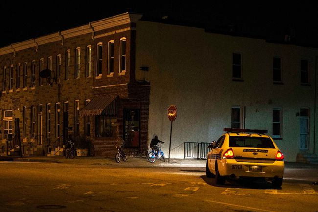 Police patrol a residential neighbourhood in east Baltimore minutes after a curfew law took effect in Baltimore August 8, 2014. REUTERS/James Lawler Duggan