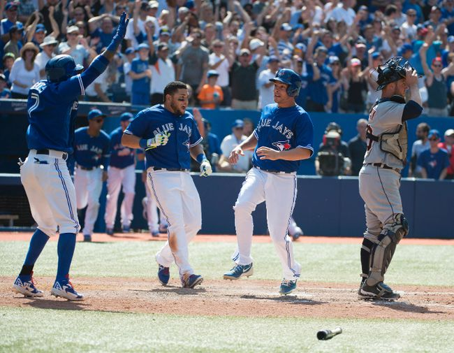 Toronto Blue Jays third baseman Danny Valencia (right) celebrates with left fielder Melky Cabrera (centre) scoring the winning run in the 10th inning against the Detroit Tigers at the Rogers Centre in Toronto, Aug. 9, 2014. (NICK TURCHIARO/USA Today)