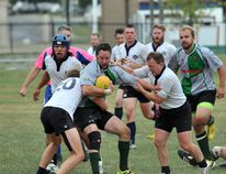 Kevin Poston, middle, of the Grande Prairie Division II Centaurs, is stopped as he tries to run the ball up field against the Edmonton Clan in Edmonton Rugby Union Division II play at Macklin Field earlier this season. The Div II squad qualified for the playoffs on Saturday. Logan Clow/Daily Herald-Tribune