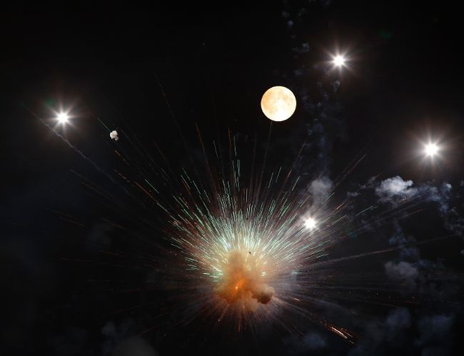 Fireworks explode in front of the supermoon outside the town of Mosta, celebrating the feast of its patron saint, in central Malta, August 10, 2014. (REUTERS/Darrin Zammit Lupi)