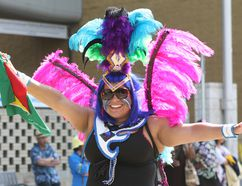 A woman decked out in sequins and feathers dances down the street during the Cariwest Grand Costume Parade on Saturday. CLAIRE THEOBALD Edmonton Examiner