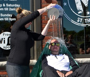 Megan McTaggart dumped a pail of cold icewater on the head of her brother, Steve Barber, as part of the ALS Challenge Wednesday outside the Midtown Tavern.  Don Biggs/Times-Journal