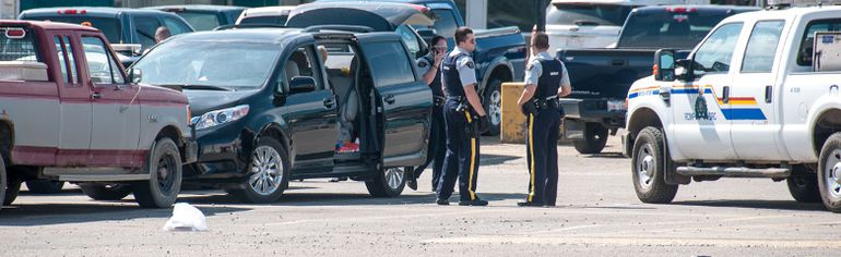 Police collect evidence in the IGA parking lot after a child was left in a van while its mother shopped. Temperatures were over 30 degrees celsius in Whitecourt. Bryan Passifiume photo | QMI Agency