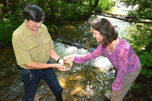 Dennis Wiseman, left, past-president of the Sydenham Sportsmen's Association, shows Owen Sound tourism marketing co-ordinator Paulette Peirol some of the smooth glacial stones that are at the bottom of shallow spawning channels for Chinook salmon near Owen Sound. DENIS LANGLOIS/SUN MEDIA