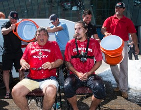 Ottawa Senators owner Eugene Melnyk and defenceman Erik Karlsson react after getting drenched with ice water after accepting the ALS Ice Bucket Challenge outside of Canadian Tire Centre on Tuesday. Errol McGihon/Ottawa Sun