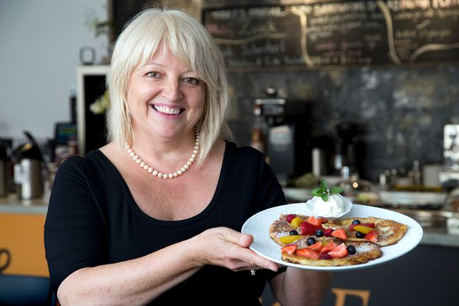 Barbara Cycz presents a plate full of apple pancakes at her Unique Food Attitudes Restaurant and takeout on Dundas St. (DEREK RUTTAN, The London Free Press)