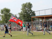The flagbearer leads Manitoba's three teams onto the diamond. (Photo by Don Radford Red River Valley Echo)