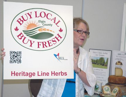 Donna Lunn, coordinator of Elgin county's Buy Local, Buy Fresh program, holds a sign featuring a QR code at an event Wednesday that launched the program's new website. (Ben Forrest, Times-Journal)
