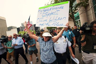 Police escort a woman away after a verbal altercation between a single pro-police demonstrator and other protestors at the St. Louis County Justice Center in Clayton, Missouri August 20, 2014.   REUTERS/Mark Kauzlarich