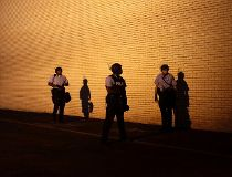 Police officers in riot gear watch demonstrators protesting against the shooting of Michael Brown from the side of a building in Ferguson