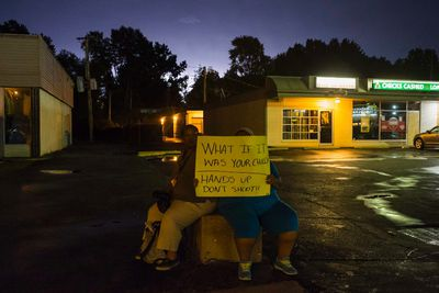 Lightning brightens the sky in the background as women hold a placard while protesting the killing of unarmed black teenager Michael Brown, in Ferguson, Missouri August 20, 2014. A thunderstorm and heavy rains struck just after dark, scattering demonstrators, including an angry crowd that had surrounded a couple carrying a pro-police sign. REUTERS/Adrees Latif