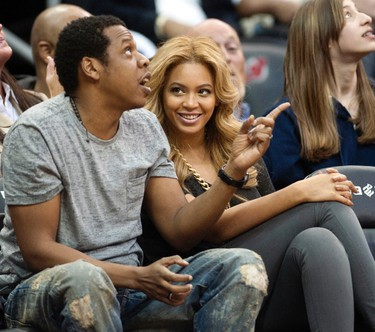 Jay Z and Beyonce watch the New Jersey Nets play the Phoenix Suns in the second quarter of their NBA basketball game in Newark, New Jersey, February 28, 2011. (REUTERS/Ray Stubblebine)