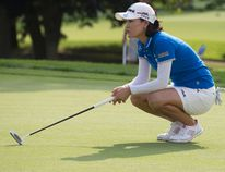 So Yeon Ryu of South Korea lines up her putt as fellow South Korean golfer Hee-Won Han watches from the edge of the 16th green during the first round of the Canadian Pacific Canadian Women's Open at the London Hunt and Country Club in London, Ont., on Thursday, Aug. 21, 2014. (Craig Glover/QMI Agency)