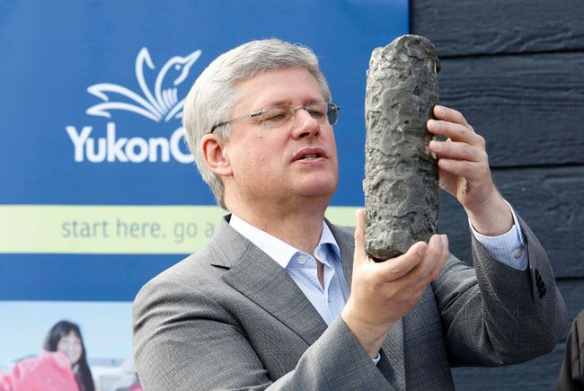 Prime Minister Stephen Harper looks at a permafrost core sample during a photo opportunity at Yukon College in Whitehorse, Yukon on August 21, 2014. (REUTERS/Chris Wattie)