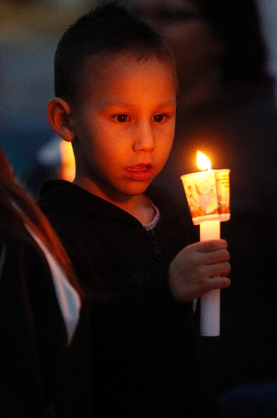 Xzavius Oxebin, 4, stares intently into the flame of his candle at a candle light vigil at Sir Winston Churchill Square in Edmonton, AB on August 21, 2014 to remember missing and murdered Aboriginal women, most recently Tina Fontaine, 15, who was found wrapped in a bag and dumped in the Red River in Manitoba on Sunday. TREVOR ROBB/Edmonton Sun/QMI Agency