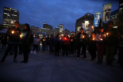 A group of people gather at Sir Winston Churchill Square in Edmonton, AB on August 21, 2014 for a candle light vigil to remember missing and murdered Aboriginal women, most recently Tina Fontaine, 15, who was found wrapped in a bag and dumped in the Red River in Manitoba on Sunday. TREVOR ROBB/Edmonton Sun/QMI Agency