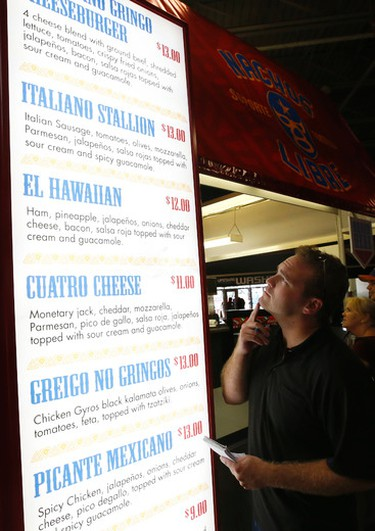 Toroto Sun reporter Matt Ingram tries out the newest food at the Canadian National Exhibition - here the American Gringo cheeseburger nachos on Monday August 18, 2014. Michael Peake/Toronto Sun/QMI Agency
