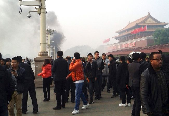 "People walk along the sidewalk of Chang'an Avenue as smoke rises in front of the main entrance of the Forbidden City at Tiananmen Square in Beijing in this October 28, 2013 file photo. China has executed eight people for ""terrorist"" attacks in its restive far western region of Xinjiang, including three who ""masterminded"" a dramatic car crash in the capital's Tiananmen Square in 2013, state media said. REUTERS/Stringer/Files"