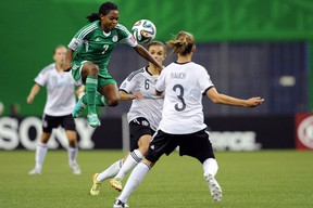 Loveth Ayila of Nigeria jumps to move the ball past Lina Magull and Felicitas Rauch of Germany during the FIFA Women's U-20 Final at Olympic Stadium on August 24, 2014 in Montreal, Quebec, Canada. (Richard Wolowicz/Getty Images/AFP)