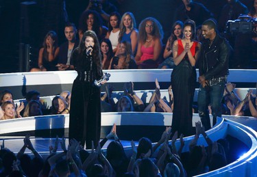 """Lorde accepts the award for best rock video for """"Royals"""" as presenters Nina Dobrev and Trey Songz listen during the 2014 MTV Video Music Awards in Inglewood, California August 24, 2014.   REUTERS/Mario Anzuoni (UNITED STATES  - Tags: ENTERTAINMENT)     (MTV-SHOW)"""