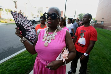 Deborah Emm fans herself as she waits in line with other people to attend the funeral for Michael Brown at Friendly Temple Missionary Baptist Church in St. Louis, Missouri August 25, 2014. The father of Michael Brown, the black teenager who was shot dead by a white police officer in Ferguson, Missouri on August 9, 2014, appealed for calm as family, politicians and activists gathered for the funeral on Monday following weeks of unrest. REUTERS/Joshua Lott
