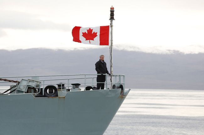 Prime Minister Stephen Harper stands on the front deck of the HMCS Kingston on Eclipse Sound, near the arctic community of Pond Inlet, Nunavut Aug. 24, 2014. Harper is on his annual tour of Northern Canada. REUTERS/Chris Wattie