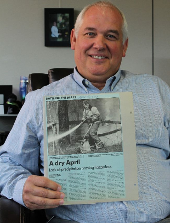 COO Brian Makey holds a 1991 Fort McMurray Today story featuring his younger self battling a Timberlea grass fire. Makey leaves the municipality in October to take over as Red Deer's fire chief. VINCENT MCDERMOTT/TODAY STAFF