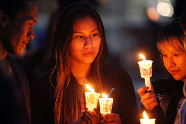 Kia Rain,14, middle, gathers with her friends at a candle light vigil at Sir Winston Churchill Square in Edmonton, AB on August 21, 2014 to remember missing and murdered Aboriginal women, most recently Tina Fontaine, 15, who was found wrapped in a bag and dumped in the Red River in Manitoba on Sunday. TREVOR ROBB/Edmonton Sun/QMI Agency