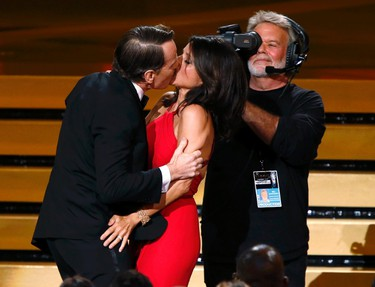 """Actor Bryan Cranston engages Julia Louis-Dreyfus in a prolonged kiss as she takes the stage to accept the award for for Outstanding Lead Actress In A Comedy Series for her role in HBO's """"Veep"""" onstage during the 66th Primetime Emmy Awards in Los Angeles, California August 25, 2014. (REUTERS/Mario Anzuoni)"""