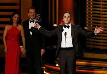"""Jim Parsons accepts the award for Outstanding Lead Actor In A Comedy Series for his role in """"The Big Bang Theory"""" as presenters Julia-Louis Dreyfus and Bryan Cranston look on during the 66th Primetime Emmy Awards in Los Angeles, California August 25, 2014. (REUTERS/Mario Anzuoni)"""
