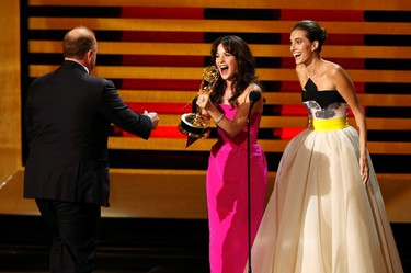 """Presenters Zooey Deschanel (C) and Allison Williams react as they award the Emmy for Outstanding Writing for a Comedy Series to Louis C.K. for """"Louie"""" during the 66th Primetime Emmy Awards in Los Angeles, California August 25, 2014. (REUTERS/Mario Anzuoni)"""