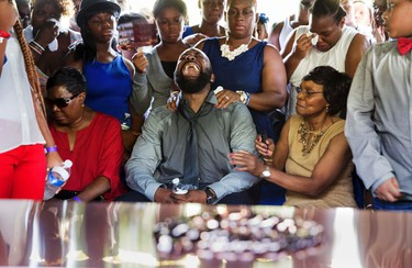 Michael Brown Sr. yells out as his son's casket is lowered into the ground at St. Peter's Cemetery in St. Louis, Missouri August 25, 2014. Family, politicians and activists gathered for the funeral of teen Michael Brown on Monday following weeks of unrest with at times violent protests spawning headlines around the world focusing attention on racial issues in the United States.  REUTERS/Richard Perry/Pool