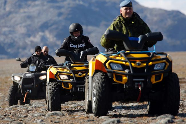 Prime Minister Stephen Harper (2nd R) rides an all terrain vehicle while observing the Operation Nanook military exercise on Baffin Island, Nunavut August 26, 2014. Harper is on the last day of his annual tour of Northern Canada. (REUTERS/Chris Wattie)