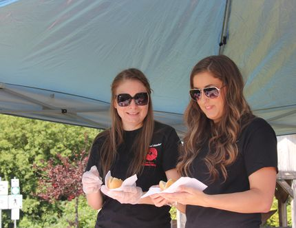 SARAH HYATT/DAILY OBSERVER Monique Trudel, volunteer, and Samantha Demers, administrative assistant for Renfrew County United Way serve up some hot dogs and hamburgers at Pembroke's Waterfront Wednesday, for the united way's 2014 campaign community barbecue. The barbecue was a soft launch for the RCUW's campaign.