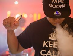 Alex Lin, 29, blows a cloud while 'vaping' or exhaling vapour from a BCV XXIX mod, or personal vapourizer, with a Patriot atomizer after attending a vapour cloud competition at the The Henley Vaporium in Lower Manhattan, New York July 26, 2014. (REUTERS/Elizabeth Shafiroff)