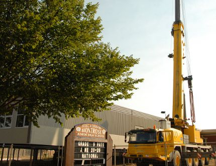 A crane from NCSG Crane and Heavy Haul Services sits beside four new modular classrooms at École Montrose School on 98 Street in Grande Prairie, Alta. on Thursday, Aug. 28, 2014. The modulars, which have been delivered over the last couple of days, are expected to be ready for students in the middle of September. In addition to the four modulars at École Montrose School, the Grande Prairie Public School District is also having one unit installed at Avondale School and two at Charles Spencer High School in October. ALEXA HUFFMAN/HERALD-TRIBUNE/QMI AGENCY