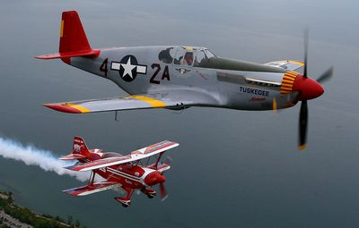 The P-51C Mustang, and Mike Wiskus in his Pitts Special fly in formation over Toronto during media flight day ahead of the Canadian International Air Show in Toronto on Friday, August 29, 2014. (DAVE ABEL/Toronto Sun)