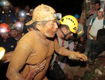 Miners and rescue workers hold a miner (front) covered in mud after he was rescued from a gold mine blocked by a landslide in Bonanza on August 29, 2014. (REUTERS/Oswaldo Rivas)