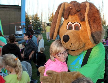 Reinfeld's Keziah Braun gives MAXX a hug during the excitement. An annual August tradition took place in Morden, Winkler and Altona, thanks to Access Credit Union. The local credit union hosted a movie in the park, showing Frozen on the big screen while handing out free popcorn, candy and hosting some great kids games on Aug. 26-28. (GREG VANDERMEULEN/Winkler Times)