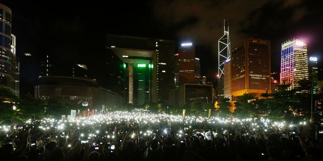 Pro-democracy protesters hold up their mobile phones during a campaign to kick off the Occupy Central civil disobedience event in front of the financial Central district in Hong Kong on August 31, 2014. (REUTERS/Bobby Yip)