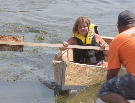 Eight-year-old Aubrey Wood crosses the finish line to win the 2nd annual Build a Boat by the Bay race Saturday afternoon at Bayfest in Port Rowan, sponsored by Port Rowan Home Building Centre.