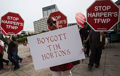 Workers march during the Labour Day March for Worker Solidarity along 100 Street in Edmonton, Alta., on Monday, Sept. 1, 2014. The march began at Sir Winston Churchill Square and ended at the Legislature Grounds. The event was staged to call attention to the current conditions and issues surrounding job availability and opportunities available to Canadians, according to the group. Codie McLachlan/Edmonton Sun/QMI Agency