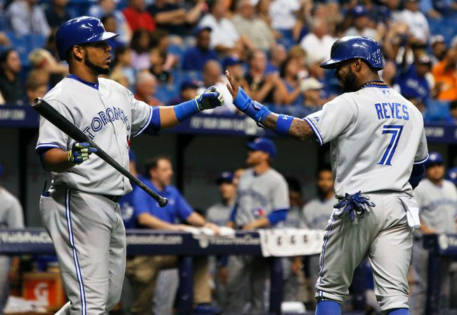 Toronto Blue Jays shortstop Jose Reyes (left) is congratulated by first baseman Edwin Encarnacion after scoring against the Tampa Bay Rays at Tropicana Field in St. Petersburg, Fla., Sept. 2, 2014. (KIM KLEMENT/USA Today)